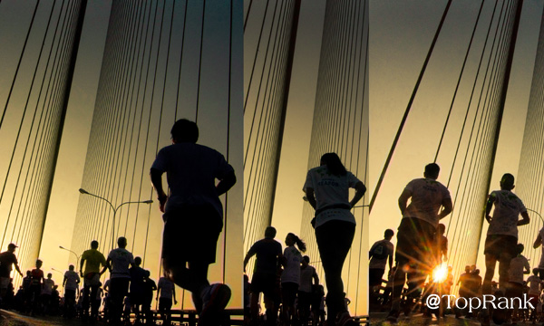 Marathon runners on bridge image.