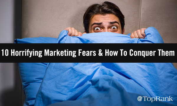 Man cowering in fear behind a blanket.