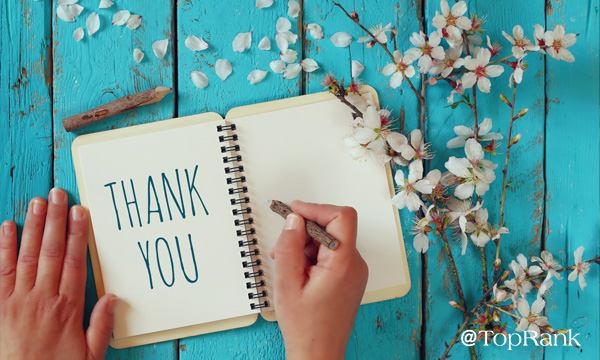 Hands writing thank you in a book surrounded by flowers image.